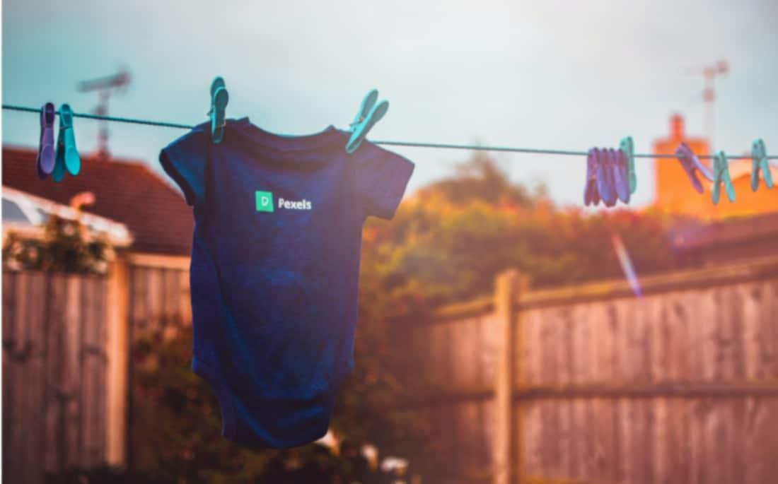 body bleu de bébé séchant au soleil suspendu par deux pinces à linge