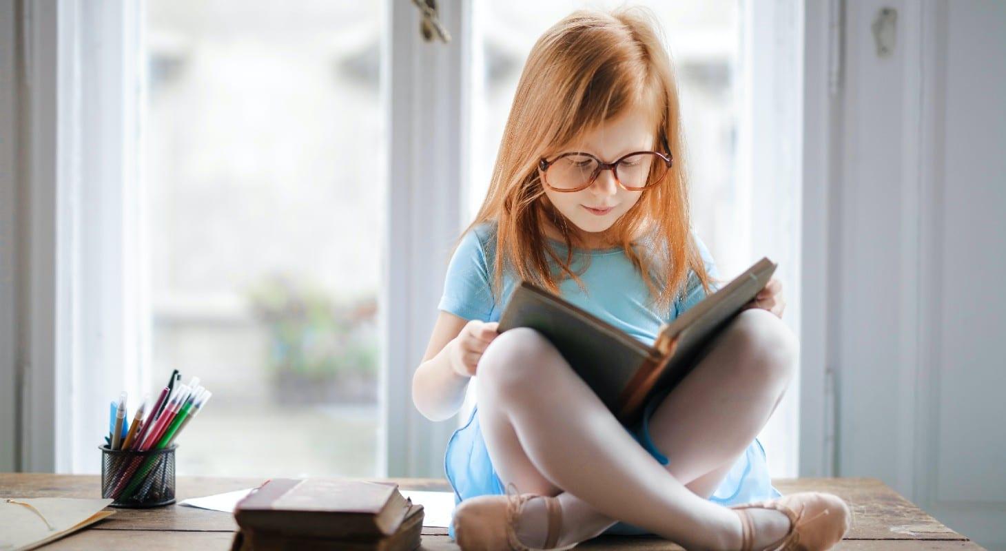 petite fille assise en tailleur avec un livre sur les