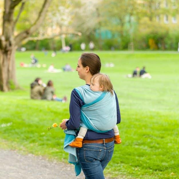 Maman qui porte son enfant grâce au sac à dos porte bébé