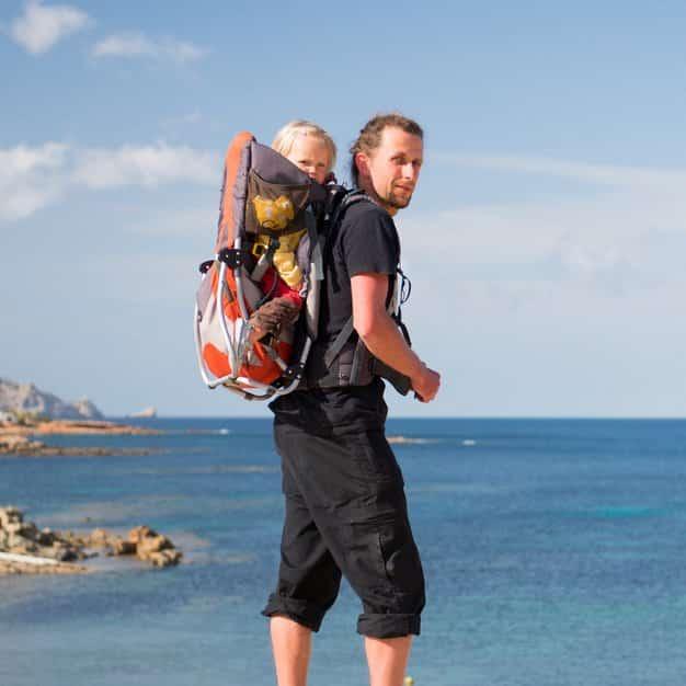 Papa porte son enfant à la plage avec son sac à dos porte bébé