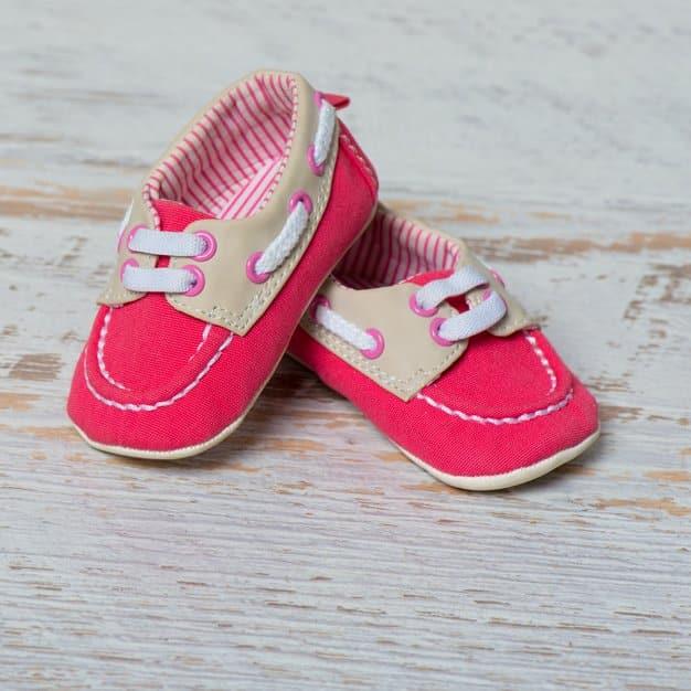 Chaussures rouges pour bébé contre un mur blanc