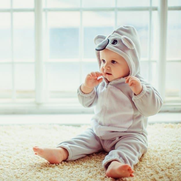 Petit bébé assit à côté de la fenêtre avec sa cape de bain