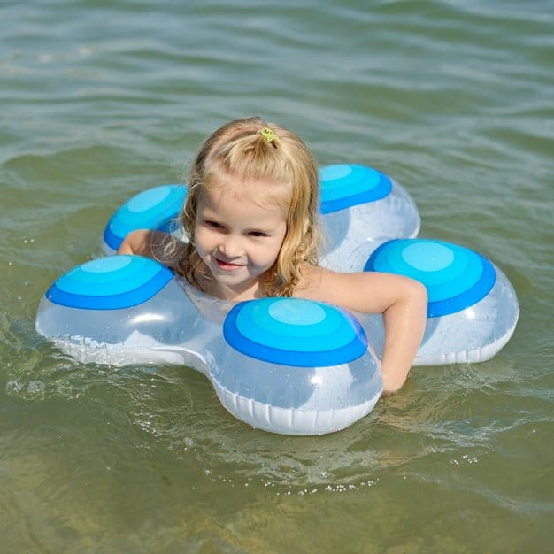 petite fille qui nage avec l'aide de sa bouée