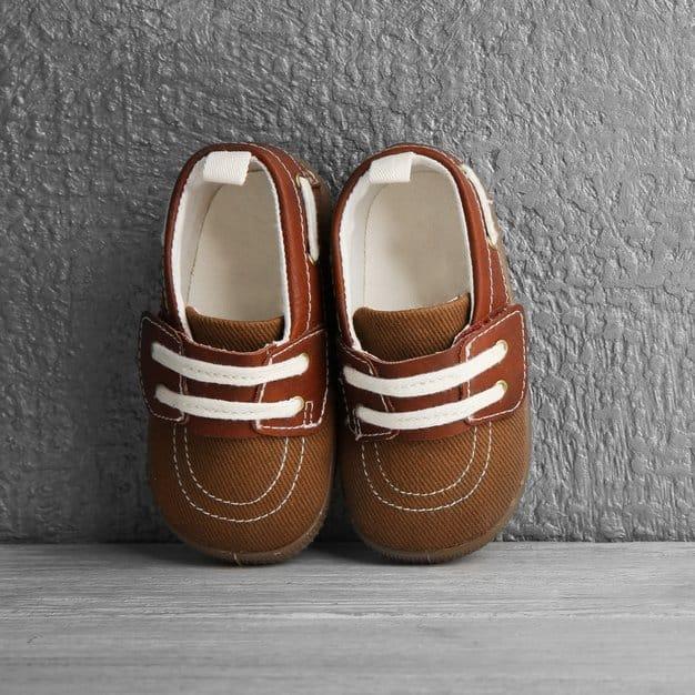 Chaussures marrons pour bébé contre un mur