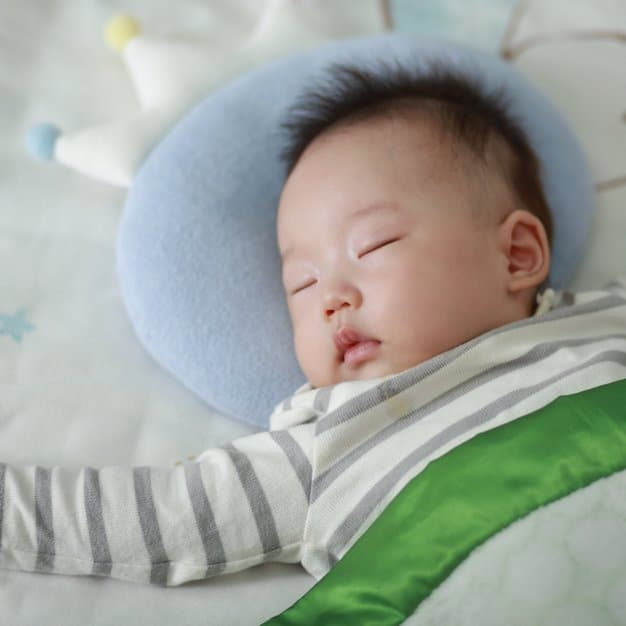 petit bébé qui dors avec sa tête sur un oreiller bleu
