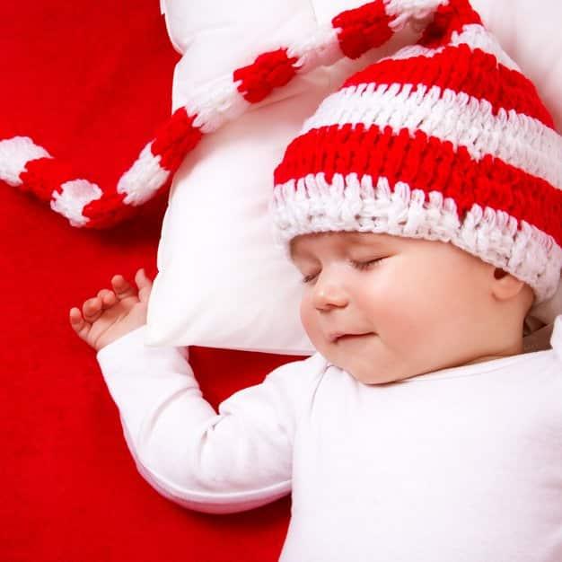 bébé qui dors avec un bonnet rouge et blanc sur un oreiller