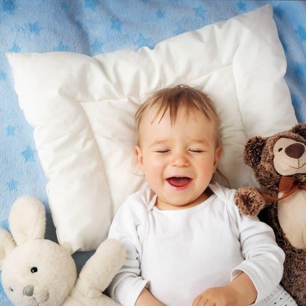 bébé qui rigole juste avant de dormir à côté de deux peluches sur un oreiller blanc