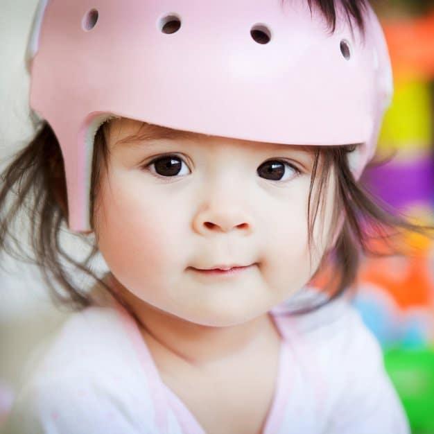 Bébé qui porte un casque rose de vélo