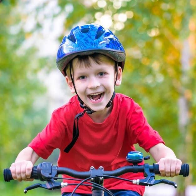 Un jeune enfant qui conduit son vélo tout en ayant un casque bleu sur sa tête