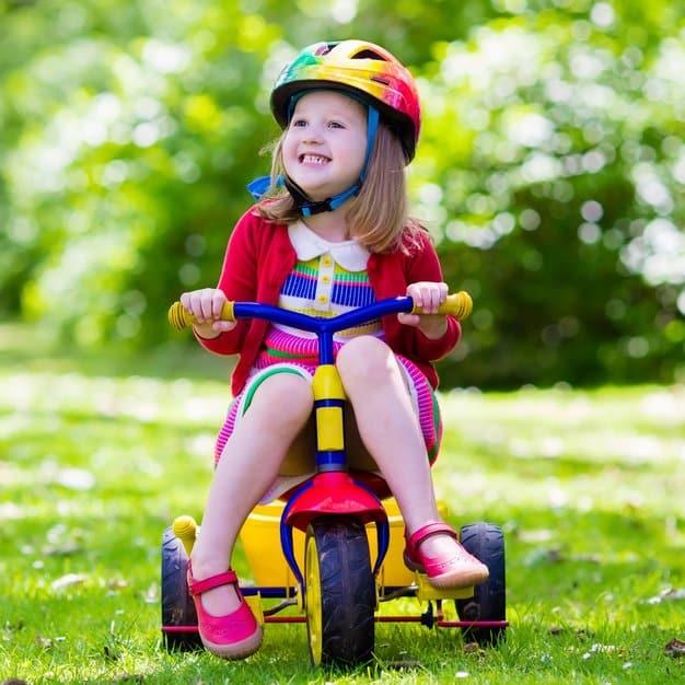 enfant qui joue avec son vélo et qui porte un casque de protection multicolore