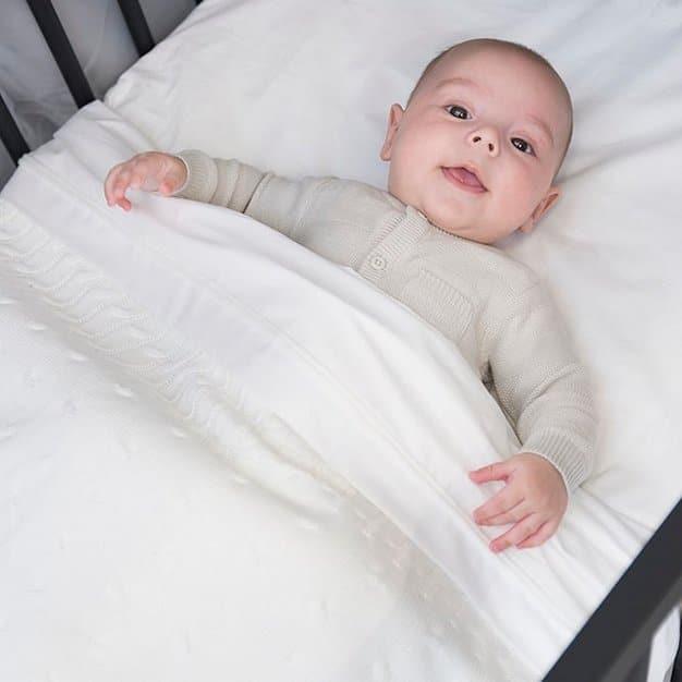 bébé regardant la caméra sur son lit avec sa couverture avant de dormir