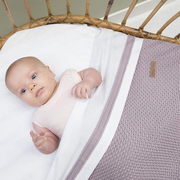 bébé sur son lit avec une couverture grise et qui parait effrayé