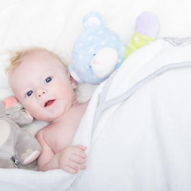 petit bébé avec les yeux ouverts qui dort à côté de peluches et couvert d'une housse