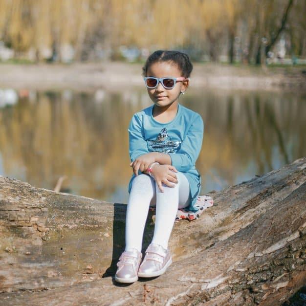 Petite fille assise dans un park portant des lunettes de soleil