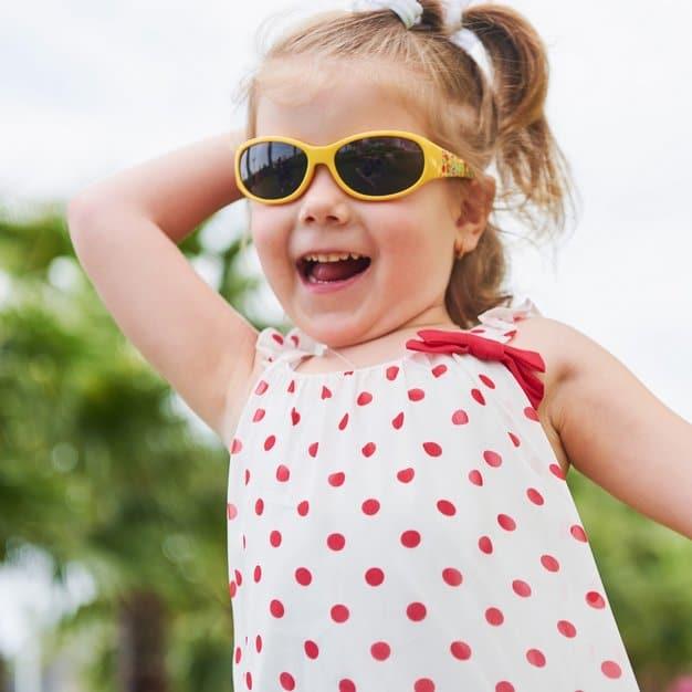 Petite fille heureuse qui court avec ses lunettes de soleil