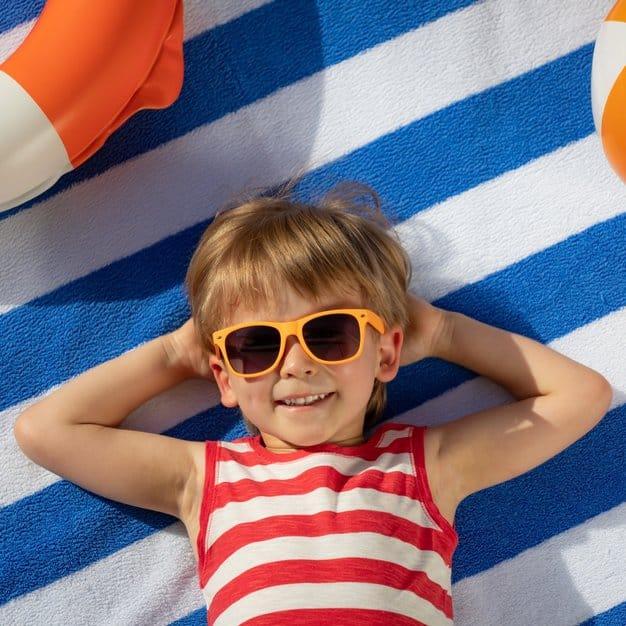 petit enfant à la plage avec des lunettes de soleil