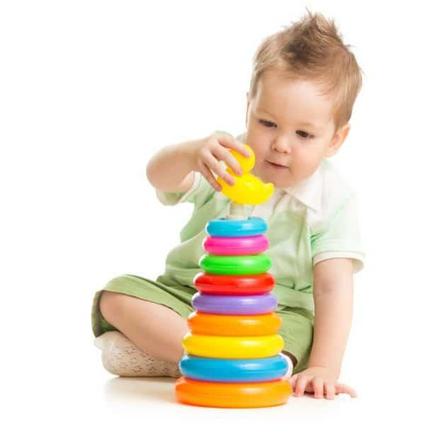 Garçon mignon jouant avec tour coloré isolé