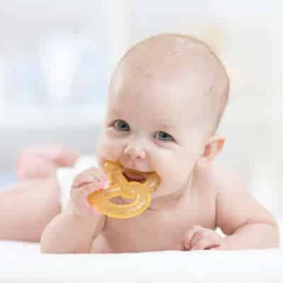Bébé qui tient un jouet dans sa bouche