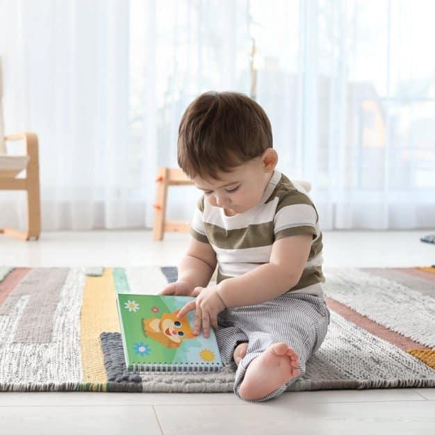 Petit bébé adorable qui s'amuse avec son livre