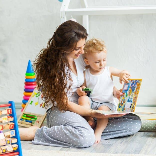 Maman montre des photos d'animaux à son enfant sur le livre pour bébé