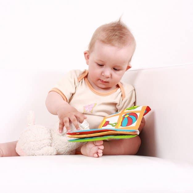 Petit enfant qui regarde une photo son livre pour bébé