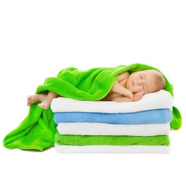 bébé qui dort sur cinq serviettes pliées et couvert d'une verte