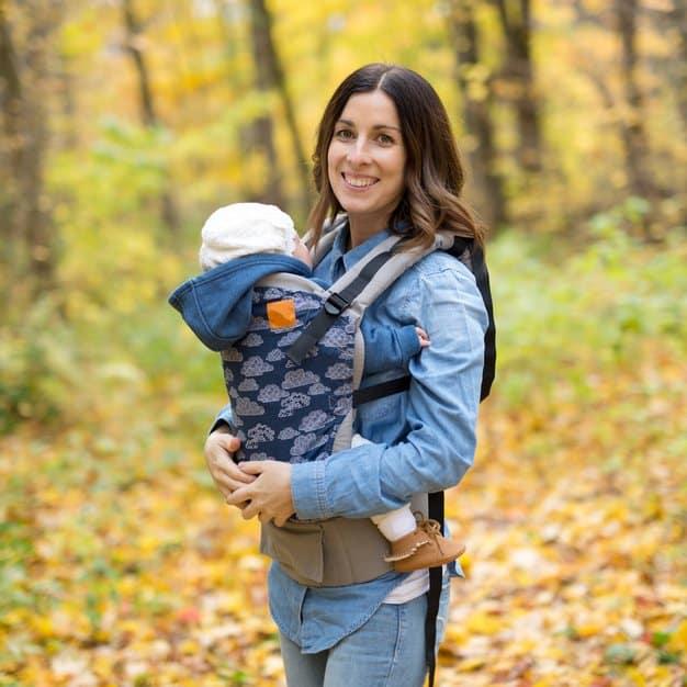 maman qui porte son enfant avec un porte bébé dorsal à la montagne
