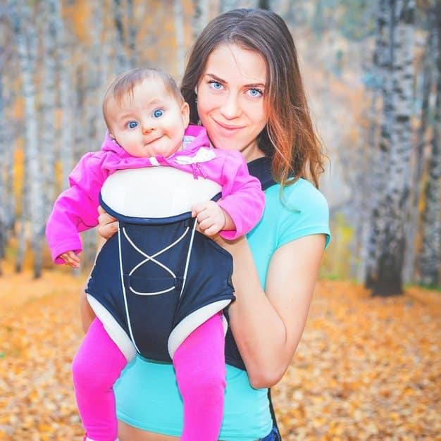 maman qui montre à la caméra comment elle porte son enfant avec un porte bébé ergonomique