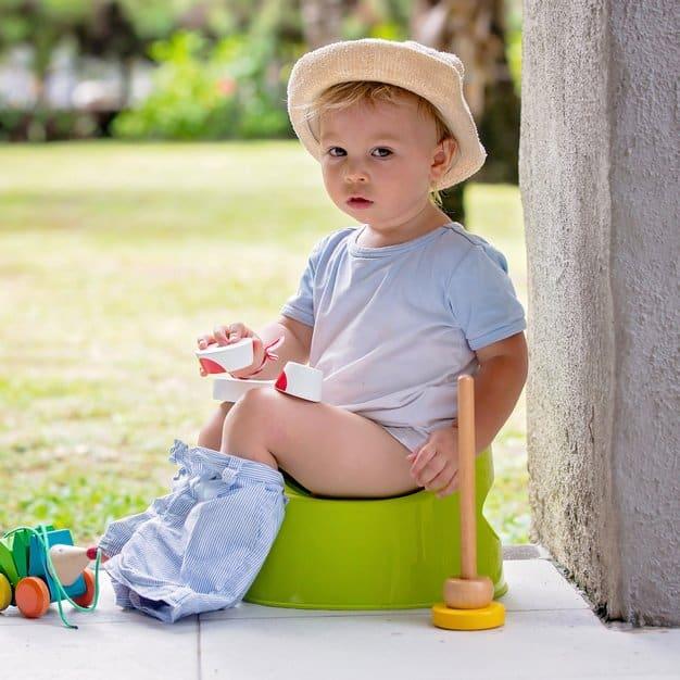 petit bébé assit sur son pot dans le jardin