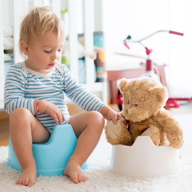 petit bébé avec sa peluche ourson assis tous les deux sur leur pot