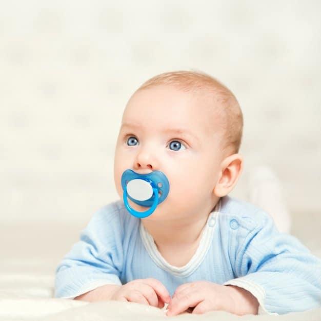 petit bébé avec une tétine blanche et bleue qui regarde devant lui