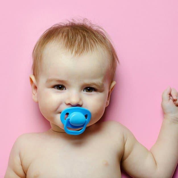 petit bébé avec une tétine bleue sur fond rose