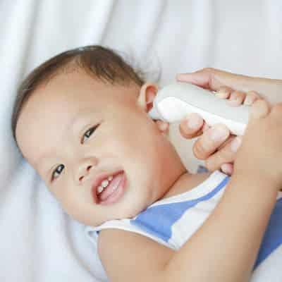 Un bébé qui sourit et qui se fait prendre sa température avec un thermomètre numérique