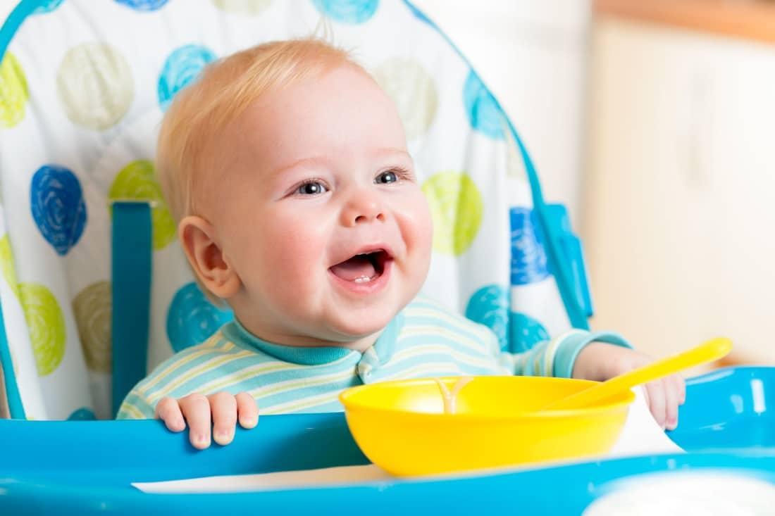bébé assis sur sa chaise haute prêt à manger