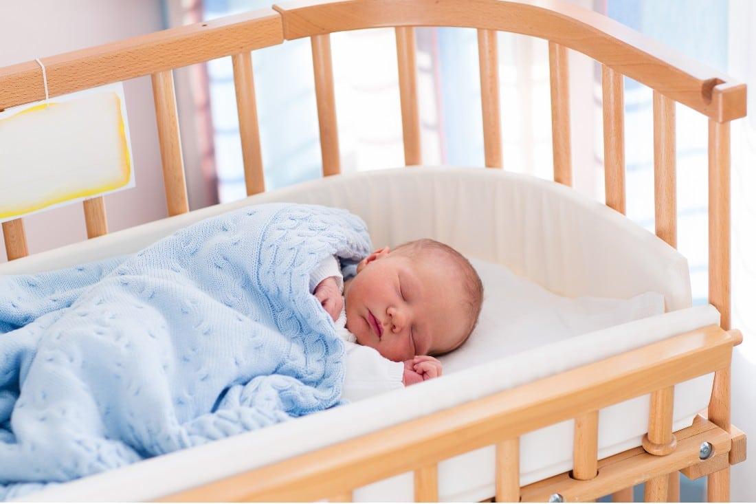 bébé dans lit avec une jolie couverture bleue