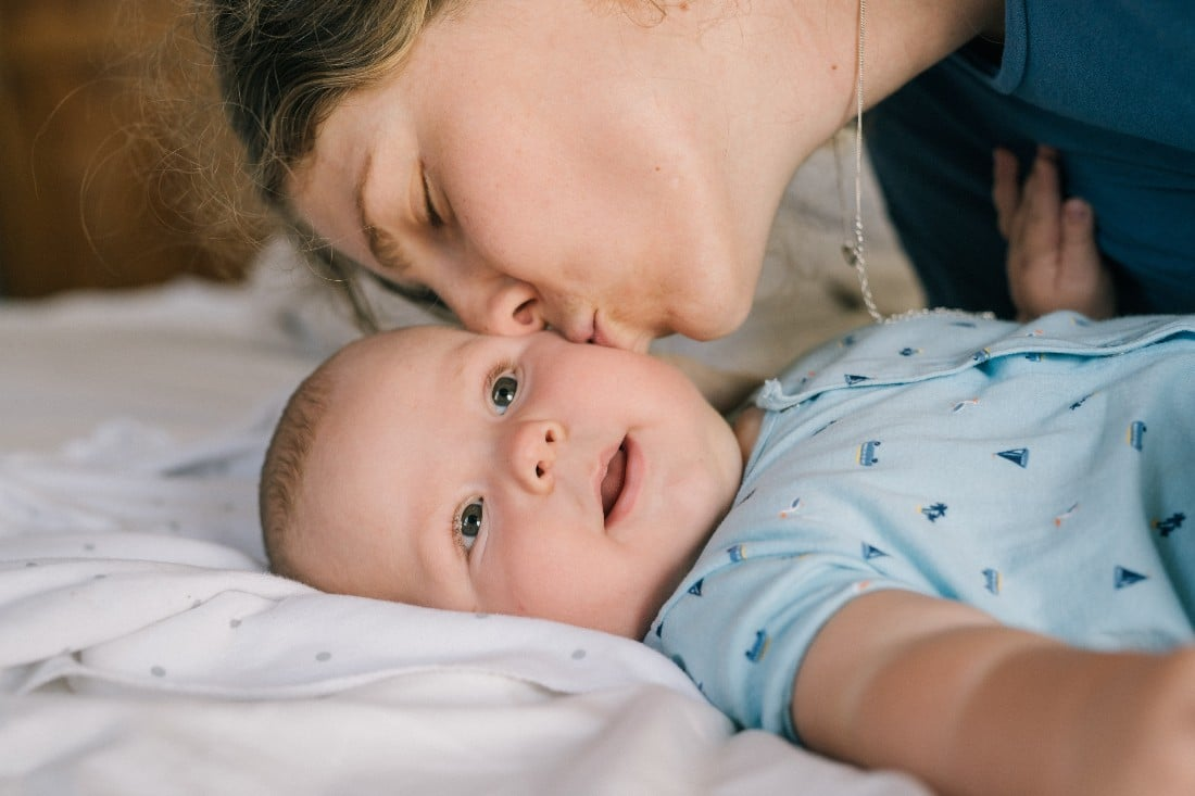 Une maman qui embrasse son béb sur la joue avant de le changer