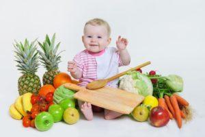 bébé au milieu de fruits et légumes