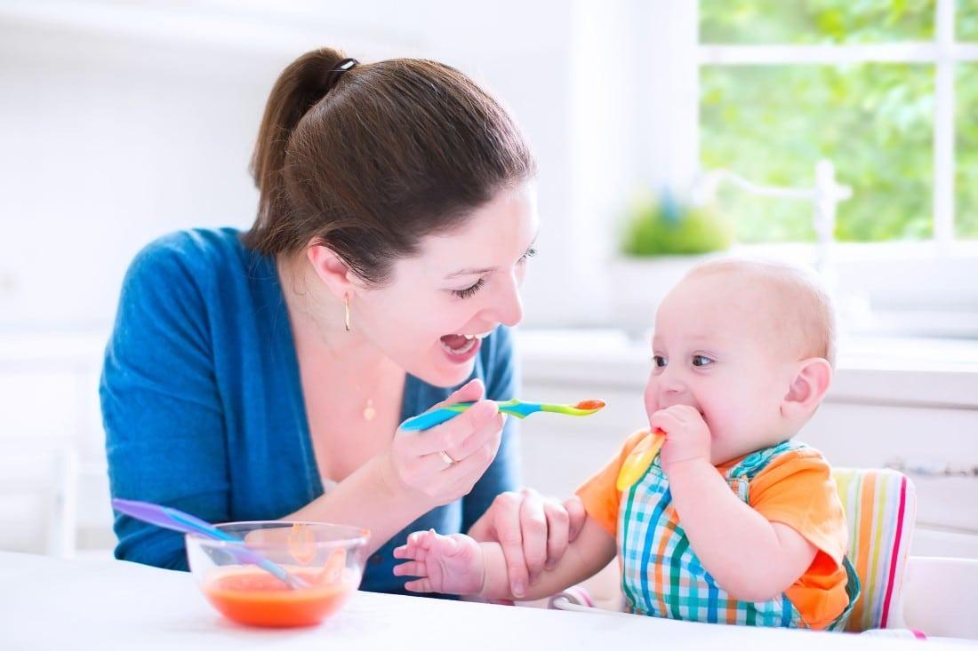 une maman qui donne à manger à son bébé