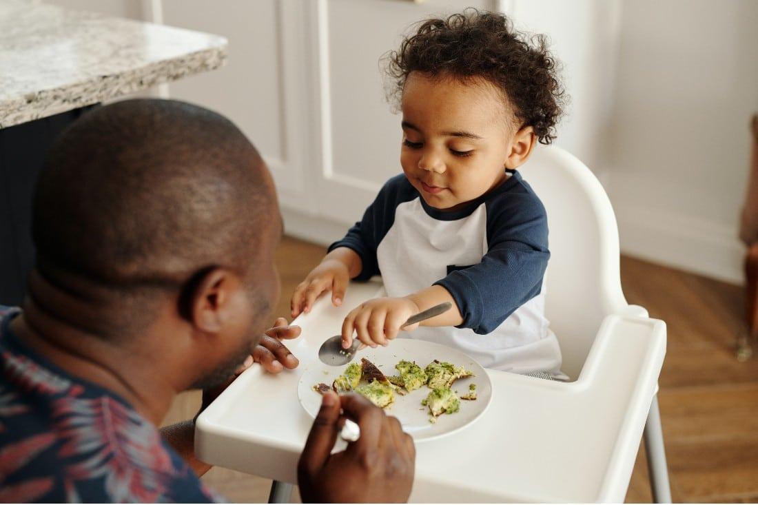 un papa qui donne à manger des légumes à son bébé