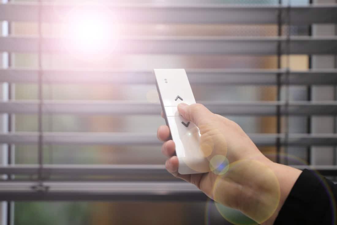 Un jeune homme qui ferme ses volets avec une télécommande pour ne pas laisser rentrer le soleil
