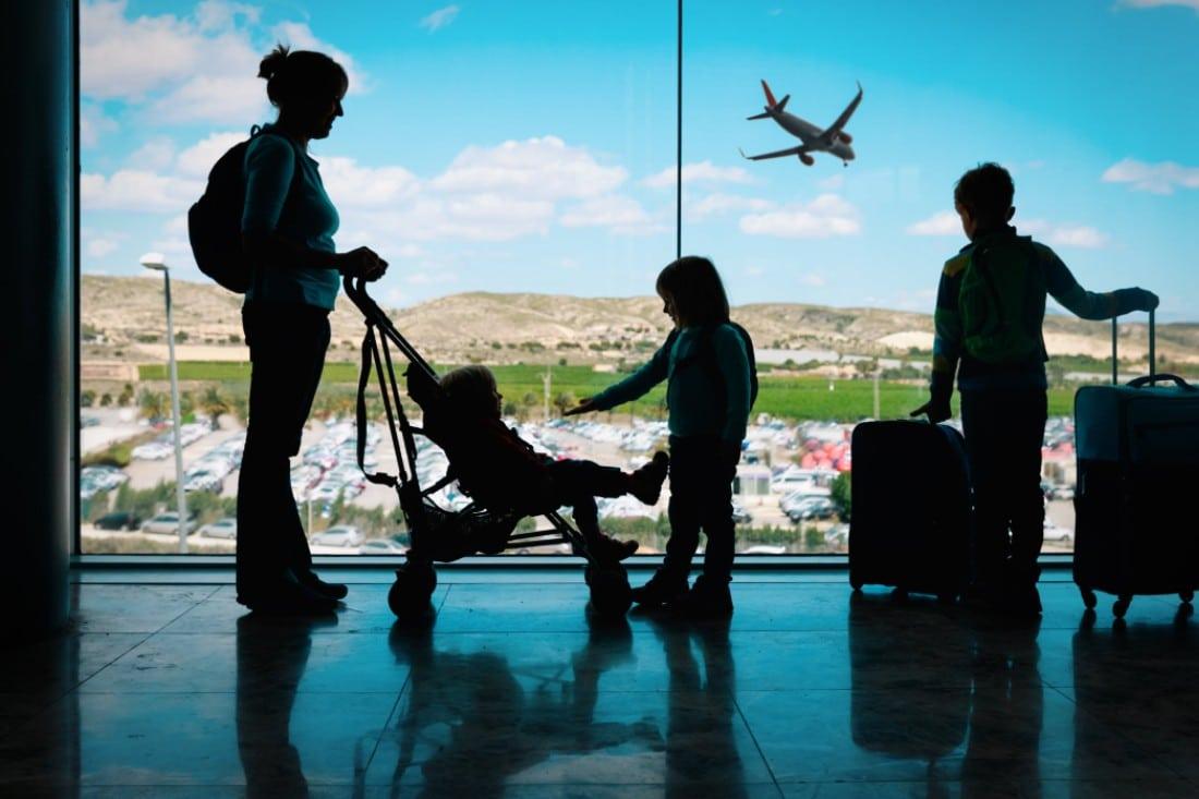 Un maman qui attend dans aéroport avec ses enfants