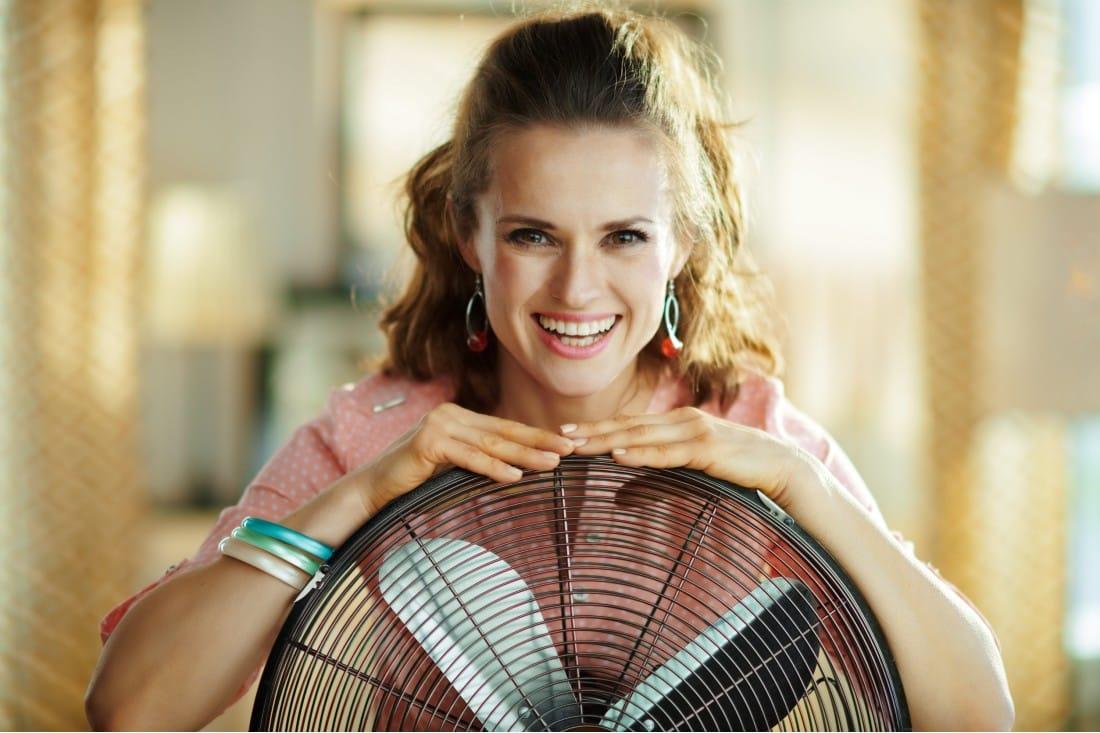 Jeune femme souriante avec un ventilateur pour rafraîchir la chambre de bébé