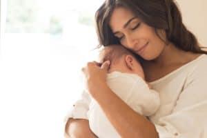 une jeune maman qui fait un câlin à son bébé