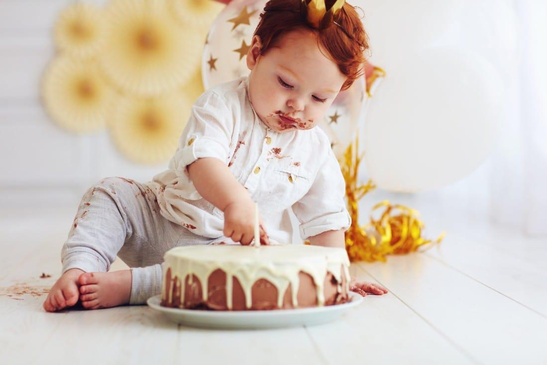 bébé assis devant son gâteau d'anniversaire avec du chocolat autour de sa bouche