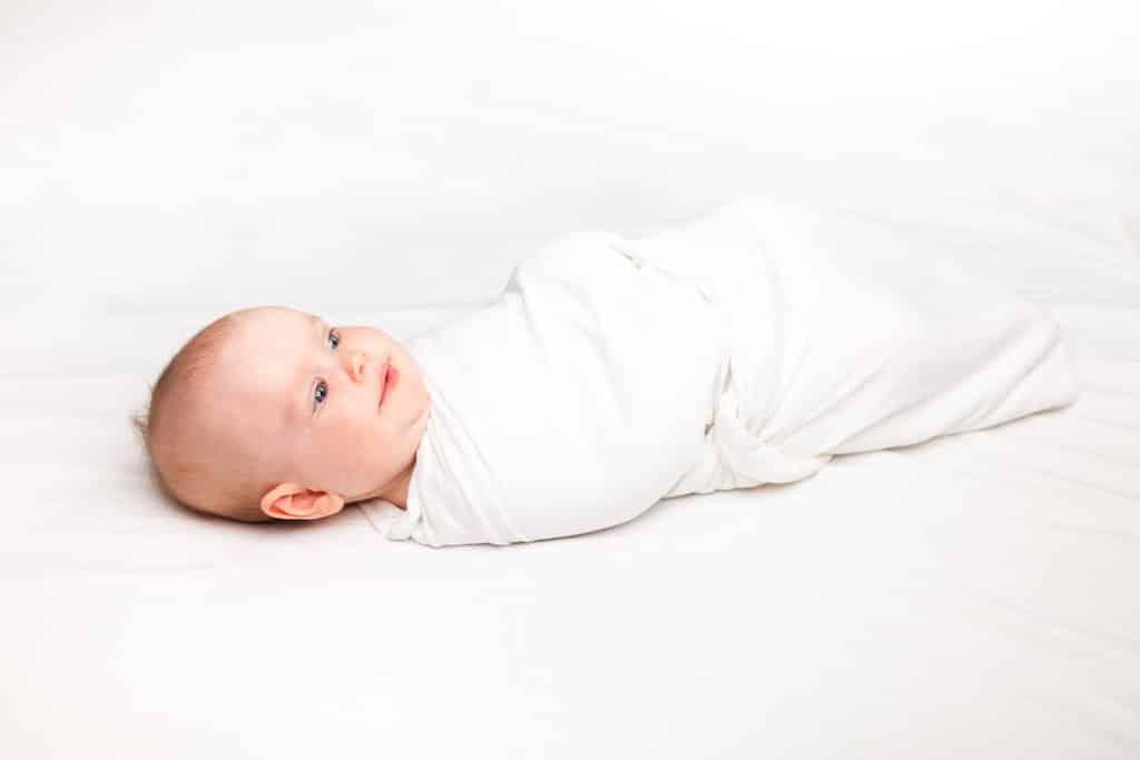 un bébé posé sur un fond  blanc est complètement emmailloté dans un lange blanc