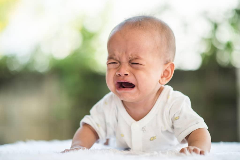 un bébé pleure, posé sur le ventre avec la tête relevée avec les forces de ses bras