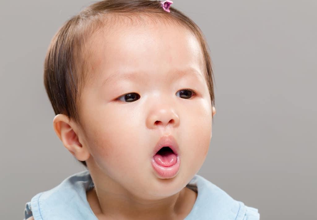 plan rapproché sur un bébé qui tousse et tire la langue pour tousser