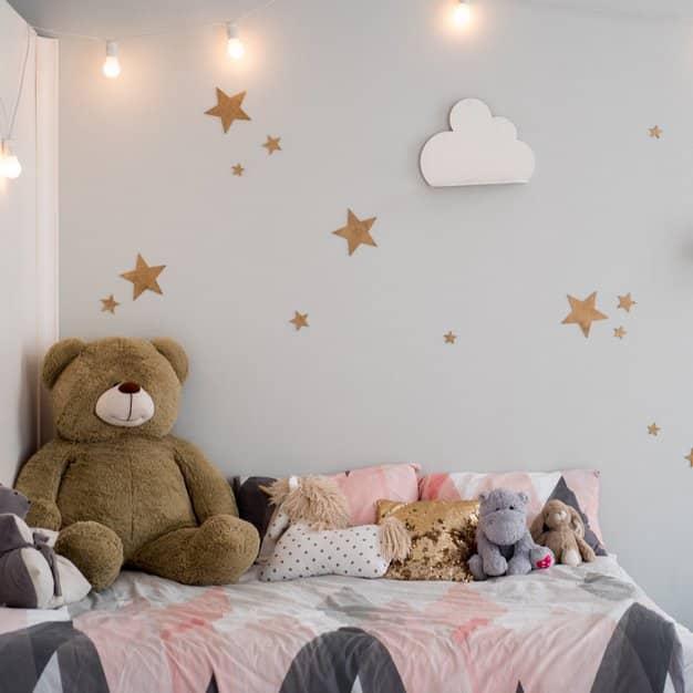 chambre d'enfant bien décorée avec un ours en peluche et d'autres accessoires