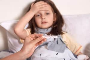 une enfant malade porte sa main sur son front. une main tient un thermomètre avec de la température juste devant la jeune fille.