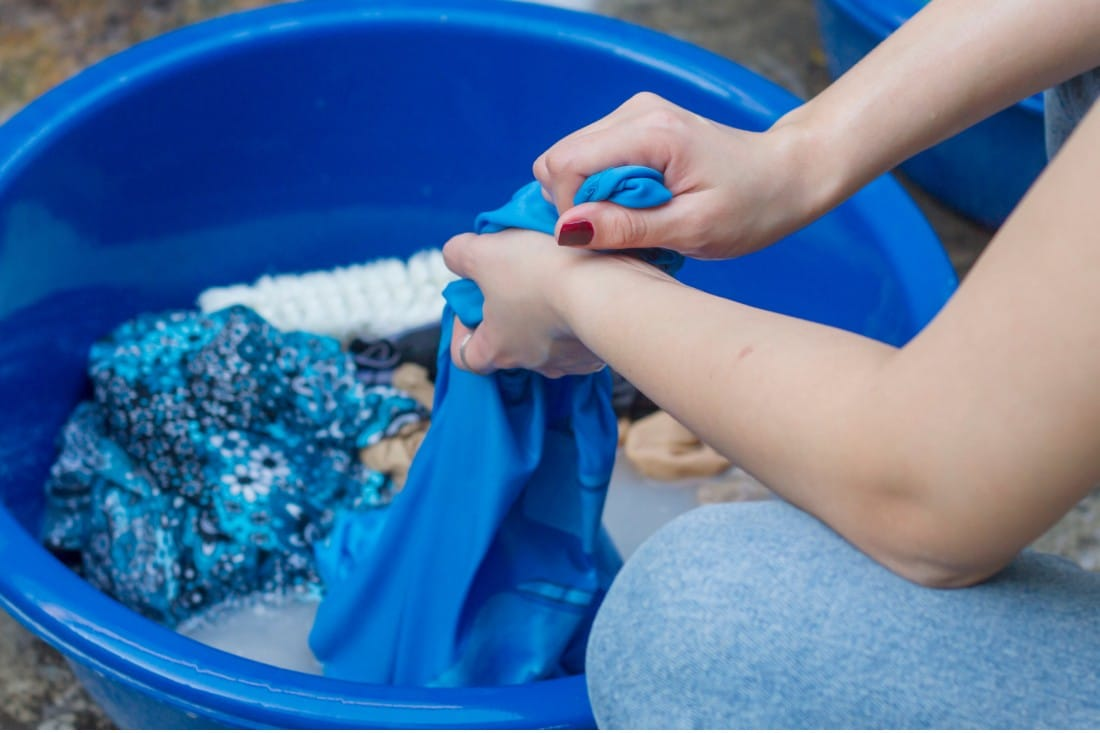 Jeune femme qui frotte du linge au-dessus d'une bassine bleue